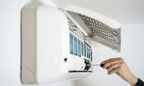 una mano con un cacciavite e accanto un condizionatore