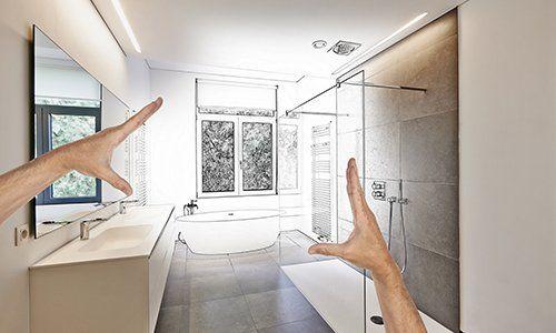due mani e vista di un bagno con due lavabi e sulla destra un box doccia
