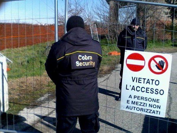 un uomo girato di spalle con un giubbotto con scritto Cobra Security