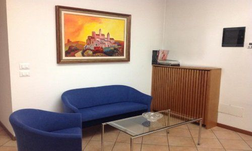 Sala d'attesa, due sofa blu,tavola bassa di vetro