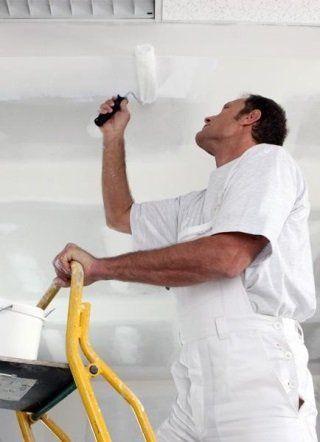 Operaio che imbianca un contro soffitto