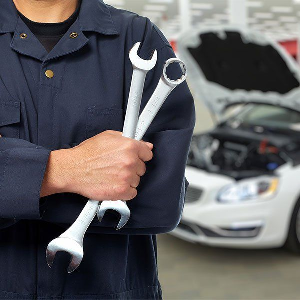 un meccanico con in mano due chiavi inglesi e dietro una macchina con il cofano aperto