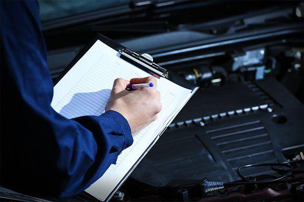 una mano di un meccanico che scrive su una cartella e dietro vista del  motore di una macchina
