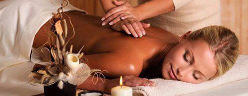 una donna sdraiata e due mani che le massaggiano la schiena