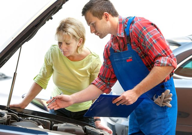 Mechanic showing something on a car to customer