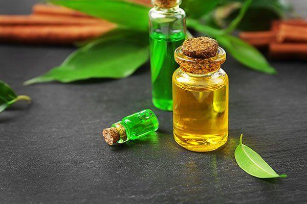 tre boccette con dei tappi in sughero con degli olii verdi e gialli e dietro delle foglie verdi