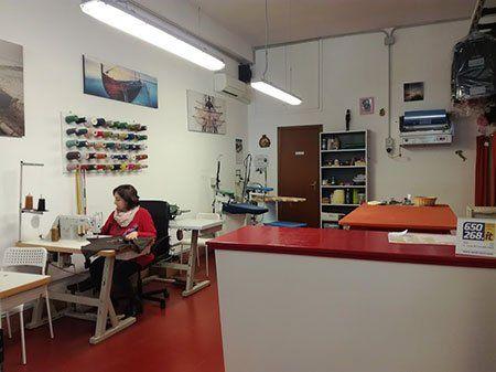 Interno del business, si vede una donna cucendo a macchina e nella parete un legno con fili di tutti i colori