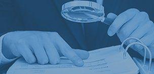 una mano che indica una pagina di un libro e l'altra con una lente d'ingrandimento