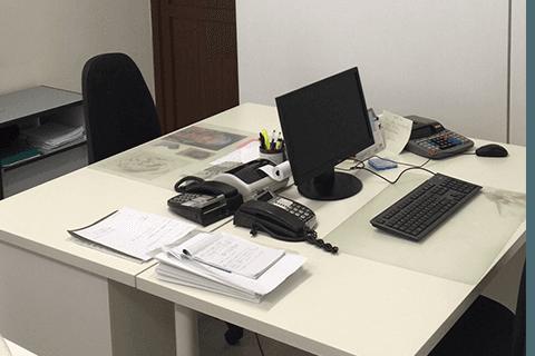 una scrivania con un monitor, un telefono e una tastiera