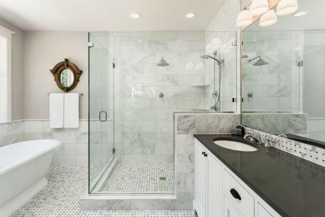 un bagno con piastrelle bianche e grigie e un box doccia
