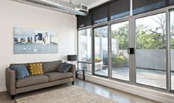 vista interna di una casa con divano grigio, cuscini, tappeto e infissi