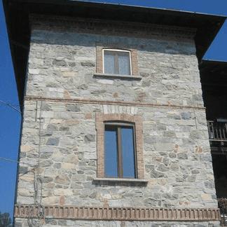 vista frontale di una casa con parete in pietra e finestre in alluminuno