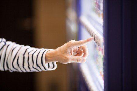 una Mano di donna mentre sta premendo un bottone di un distributore automatico