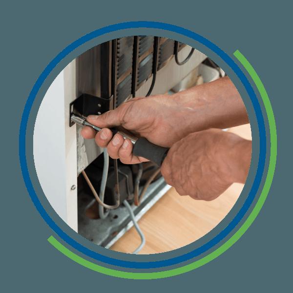 Un tecnico avvita una componente di un frigorifero