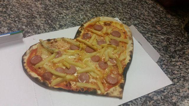 una pizza con patatine a forma di cuore