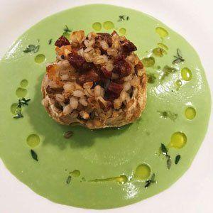 Un piatto di zuppa di color verde con crostino e pancetta