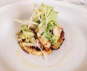 Un piatto a base di pesce con insalata