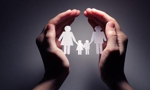 Mani proteggendo una famiglia di carta