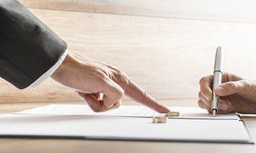 Un documento, due alleanze di nozze, un dito di uomo segnalando, una donna firmando