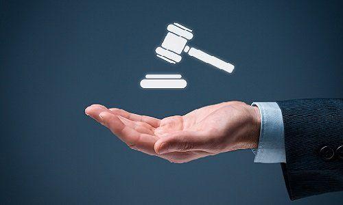 Una mano, un martello di giustizia di carta sopra