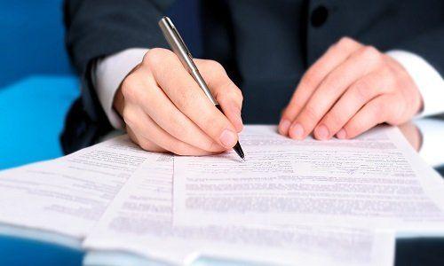 Uomo firmando vari documenti