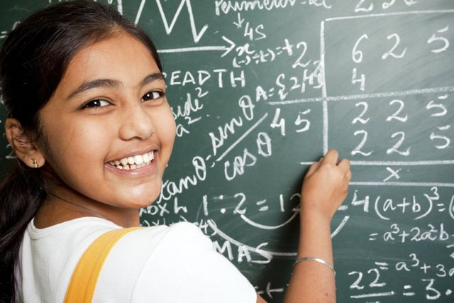 smiling girl in front of maths blackboard