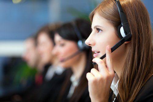primo piano di una giovane donna mentre risposta al telefono con colleghi in un call centre