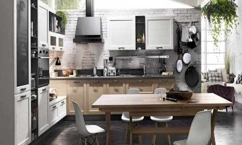 Cucina di legno bianco, parete di pietra bianca e completamente equipaggiata