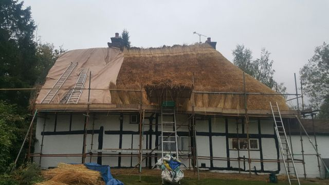 A cottage being re-thatched