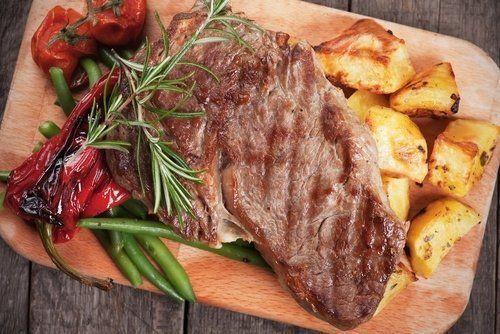 un tagliere con una bistecca e delle patate al forno