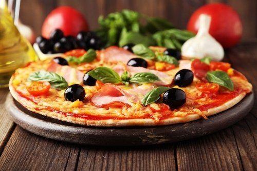 un tagliere di una pizza con sopra delle olive e del  basilico ed del prosciutto