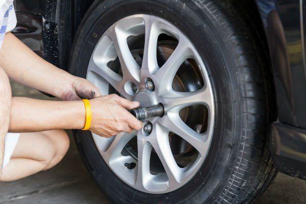 una mano con un attrezzo che avvita e bulloni di una ruota