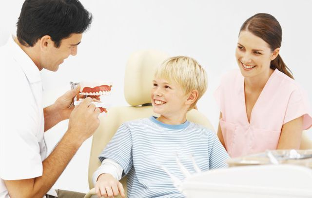 Dentist and assistant with young child during tooth replacement in High Point, NC
