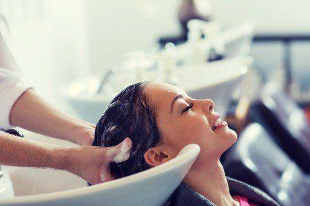 Un parrucchiere lava i capelli di una cliente