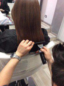 Parrucchiera mette in piega in capelli di una cliente