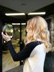 ragazza con capelli biondi mossi che si guarda allo specchio