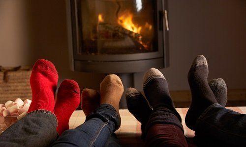 quattro piedi con calzini davanti ad una stufa a pellet