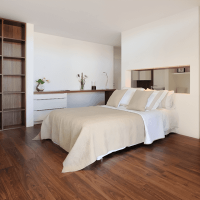 A bedroom with a dark hardwood floor