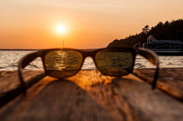 degli occhiali da sole di fronte a un tramonto